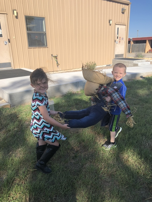 Kyndal and Tatum carry their scarecrow to the front of the Kindergarten Building.