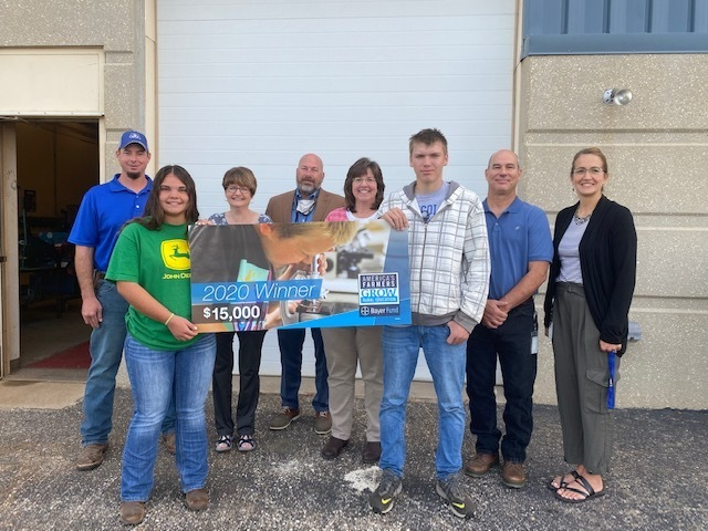 Metal Students, Natalia and Fallon, hold the $15,000 Award sign with board members, John Buttenhoff, Jeanna Eckhart and Patti Winters; Superintendent, Scott Crenshaw; Metals Instructor, James Lange; and LJSHS Principal, Christi Walter